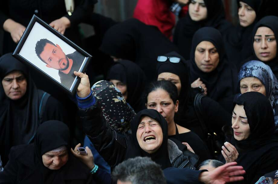 A relative of Samer Huhu who was killed in a twin bombing attack that rocked a busy shopping street in the area of Burj al-Barajneh waves his portrait as she mourns during his funeral in the southern suburb of the capital Beirut