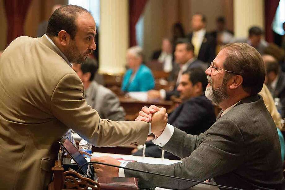 Assemblyman Adrin Nazarian, D-Los Angeles (left), and Sen. John Moorlach, R-Costa Mesa, shake hands after Moorlach crossed party lines to vote for a bill authored by Nazarian. Photo: Max Whittaker/CALmatters