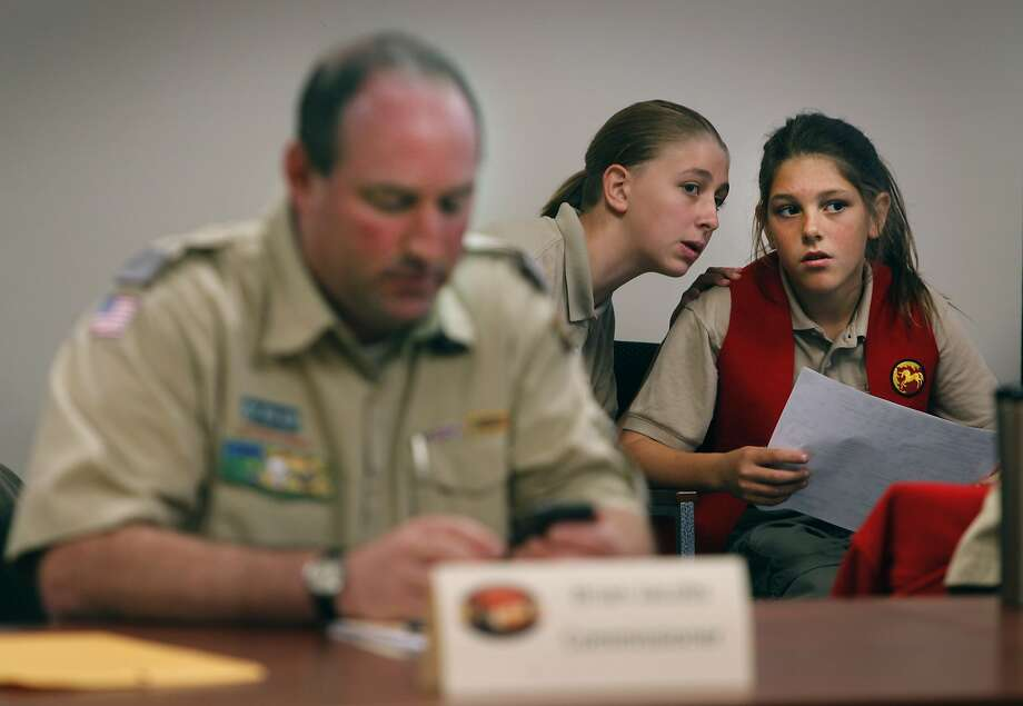 Allie Westover, 13, whispers to her sister Skyler, 10, behind council commissioner Brian Jacobs, who was representing the girls, at a meeting of the Redwood Empire Council of the Boy Scouts of America in Santa Rosa, Calif. on Friday, Nov. 13, 2015. Girls in the scout-sponsored Learning for Life program are seeking full admission to the Boy Scouts. Photo: Paul Chinn, The Chronicle