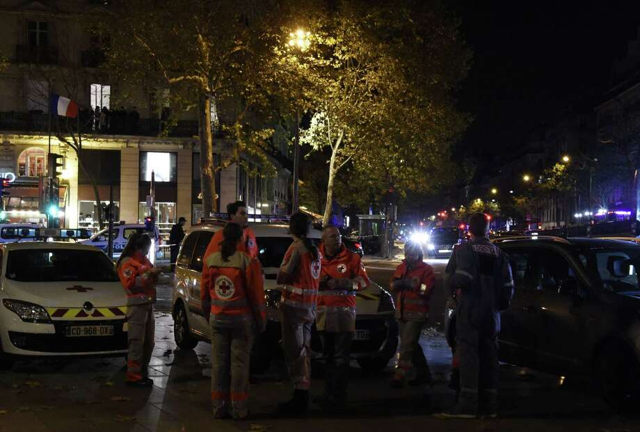Police officers and rescue workers stand near the site of a shooting near Place de la Republique square in Paris on November 13, 2015. At least 18 people were killed in several shootings and explosions in Paris today, police said.  AFP PHOTO / DOMINIQUE FAGETDOMINIQUE FAGET/AFP/Getty Images Photo: DOMINIQUE FAGET, AFP / Getty Images / AFP
