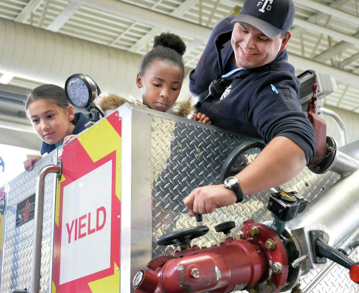 Firefighter Matt Ryan, right, gives students Inari Sohn, left, and De'Ajinay Porter a close up look at a ladder truck as winners of the annual fire prevention poster contest tour the Troy Central Fire House Friday Nov. 13, 2015 in Troy, NY. (John Carl D'Annibale / Times Union)