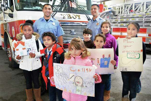 Firefighter Jarred Collins, left, and Capt. Matt Dudek with fire prevention poster contest winners, from left, De'Ajinay Porter, Ilan Payan, Morgan Mamone, Louis Katz, Ryan Clemente, Aubrielle Stemp and Inari Sohn at the Troy Central Fire House Friday Nov. 13, 2015 in Troy, NY.   (John Carl D'Annibale / Times Union) Photo: John Carl D'Annibale / 00034129A