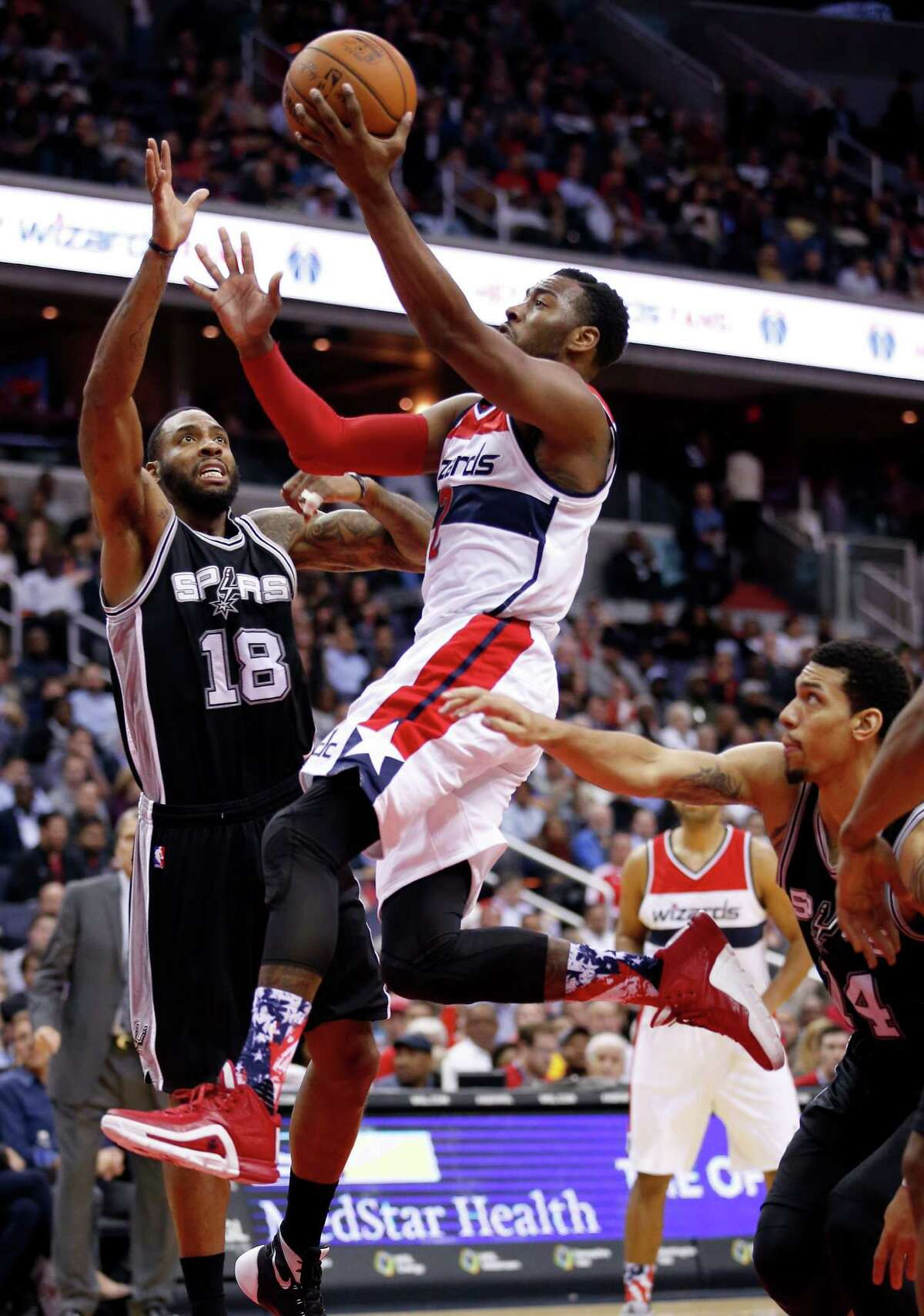 Wizards guard John Wall shoots between Spurs forward Rasual Butler (18) and guard Danny Green (14) during the second half on Nov. 4, 2015, in Washington. The Wizards won 102-99.