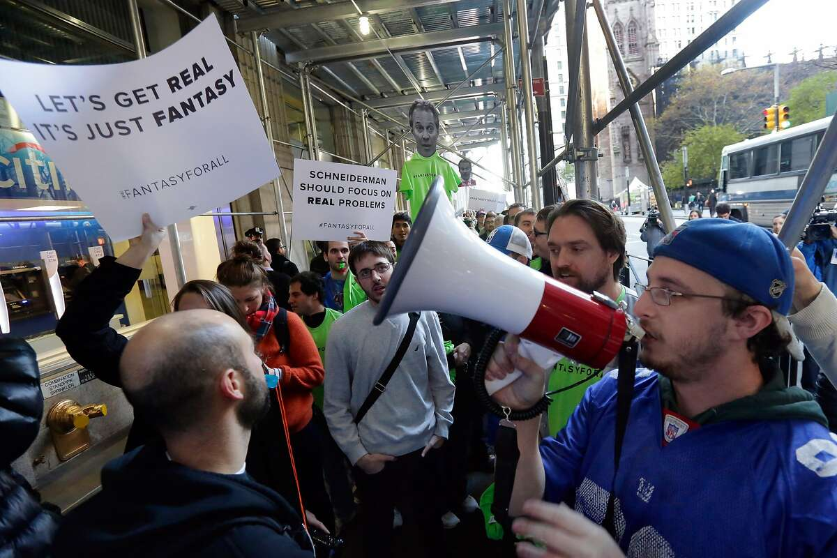 Fantasy sports fans demonstrate outside the Financial District offices of New York state Attorney General Eric Schneiderman, in New York, Friday, Nov. 13, 2015. Schneiderman's decision that daily fantasy sports betting sites FanDuel and DraftKings are illegal gambling operations in his state is a blow to the companies, but the multibillion-dollar industry could have more legal headaches yet to come. (AP Photo/Richard Drew)