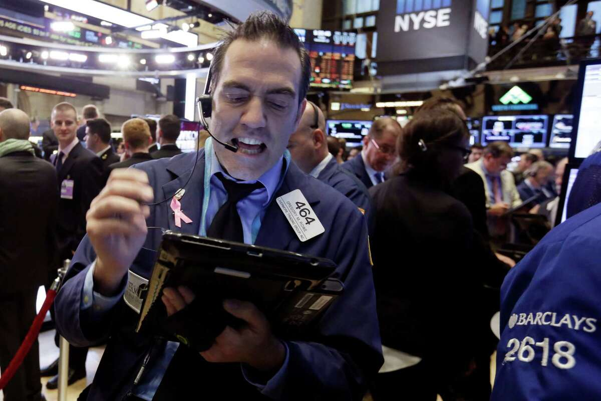 Trader Gregory Rowe, left, works on the floor of the New York Stock Exchange, Friday, Nov. 13, 2015. Sharp declines in retailers were dragging the stock market lower in early trading as investors worry that holiday sales could slump. (AP Photo/Richard Drew) ORG XMIT: NYRD118