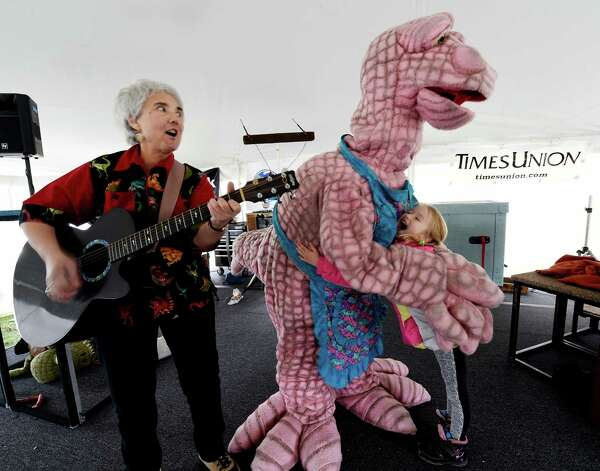 """Michele Valeri, left plays a tune as Kasia Masnik, 6, gets close up and personal with Ingrid """"Maiasaura"""" Crepeau at the Science Festival held at the Museum of Innovation and Science Nov. 13, 2015 in Schenectady, N.Y.  The Science Festival runs through Sunday at the Museum.  (Skip Dickstein/Times Union) Photo: SKIP DICKSTEIN / 00034237A"""
