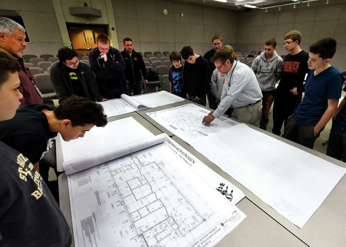 Students from Mohonasen High School learn the intricacies of reading blueprints and seeing the end result as their new building, the Center for Advanced Technology is built in the rear of the school property under the guidance of Marc Rivers, right and Tom Robert, left of U.W. Marx Friday Nov. 13, 2015 in Rotterdam, N.Y. (Skip Dickstein/Times Union)