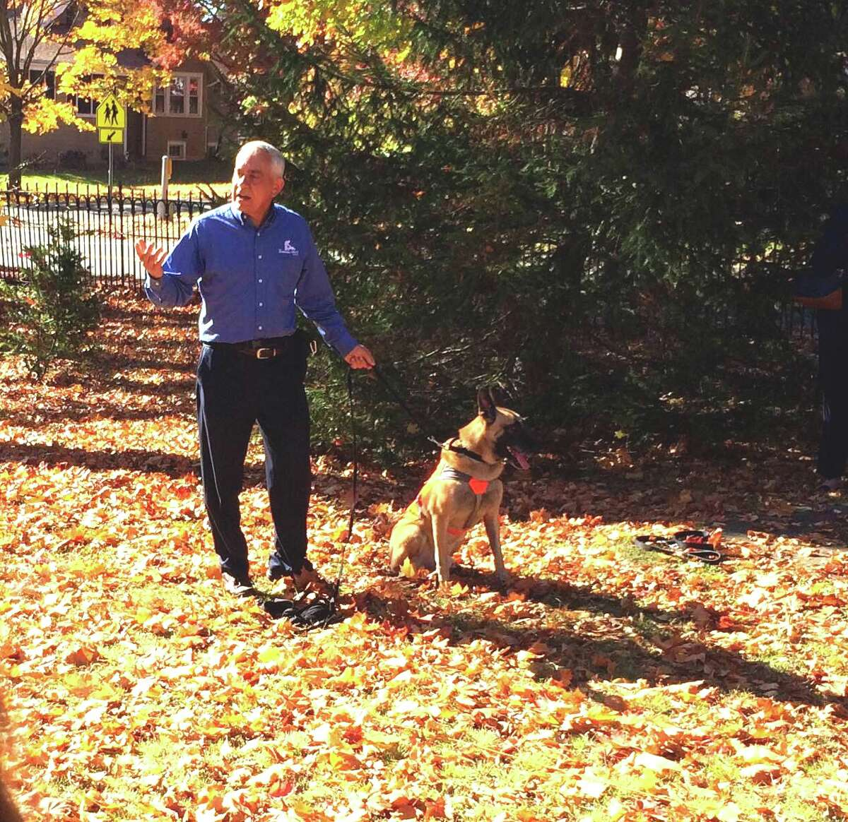 Col. Perry Baltimore from the Marshall Legacy Institute with Dino, a mine-detecting German shepherd at the Beacon School.