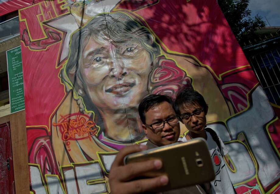 People mark a historic day Friday in the foreground of a portrait featuring Myanmar's opposition leader, Aung San Suu Kyi, after the landslide election in Yangon. Photo: Gemunu Amarasinghe, STF / AP
