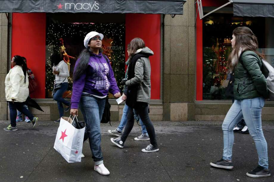 A woman walks out of a Macy's department store in New York with a shopping bag Thursday. The Commerce Department said Friday that retail sales rose a seasonally adjusted 0.1 percent last month. But meager inflation has downplayed the extent of consumer spending, as the retail sales report is not adjusted for price changes. Photo: Mark Lennihan /Associated Press / AP