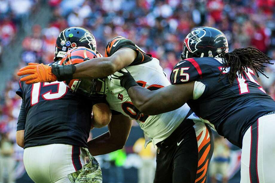 Bengals defensive end Carlos Dunlap, center, who is tied with J.J. Watt for second on the NFL sack list, showed the Texans what a force he can be last year by beating Derek Newton, right, to get to the quarterback. Photo: Smiley N. Pool, Staff / © 2014  Houston Chronicle