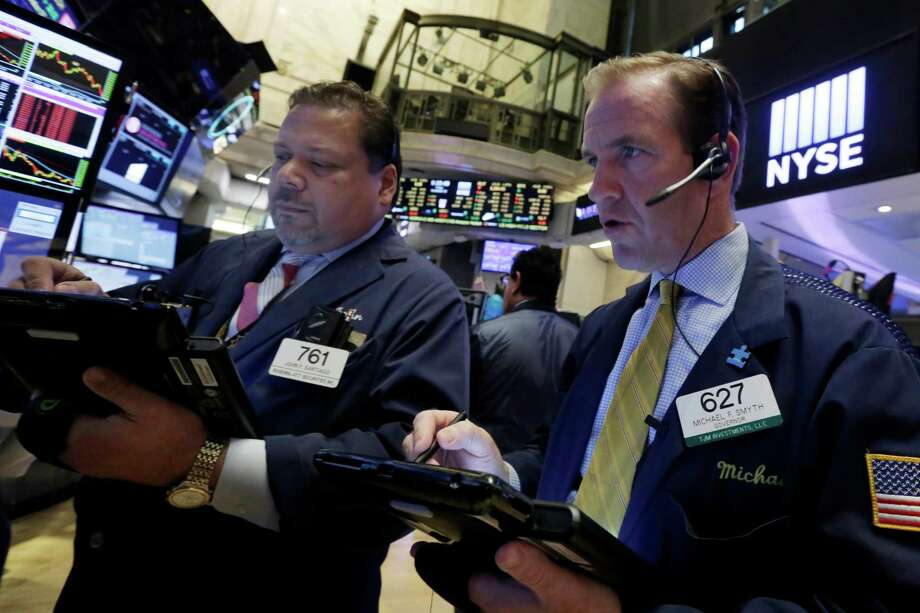 Traders John Santiago, left, and Michael Smyth work on the floor of the New York Stock Exchange, Friday, Nov. 13, 2015.  Sharp declines in retailers were dragging the stock market lower in early trading as investors worry that holiday sales could slump. (AP Photo/Richard Drew) Photo: Richard Drew, STF / AP