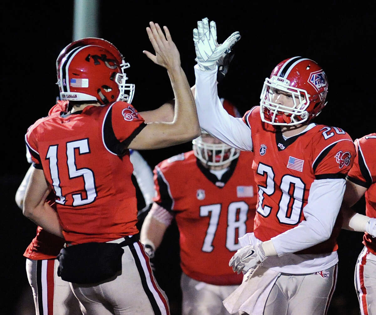 New Canaan quarterback Michael Collins (#15), left, high-fives teammate Kyle Smith (#20) just after Collins connected with Smith on a pass play for a first quarter touchdown during the high school football game between New Canaan High School and Fairfield Ludlowe High School at New Canaan, Conn., Friday night, Nov. 13, 2015.