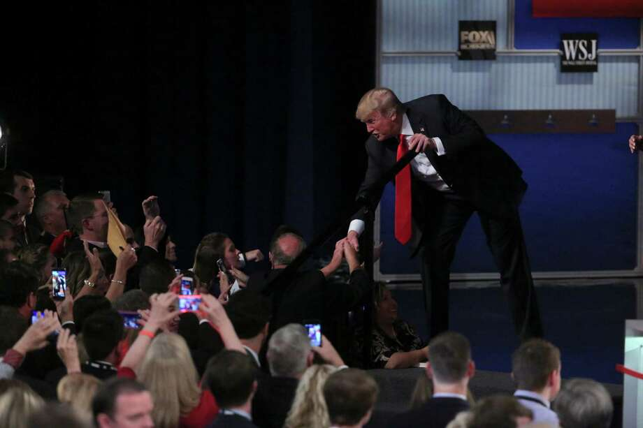 Donald Trump shakes hands with people in the crowd after the Republican presidential debate in Milwaukee, Nov. 10, 2015. A reader says the media panel missed a chance to ask some crucial questions about his immigration proposals. Photo: MICHAEL APPLETON /New York Times / NYTNS
