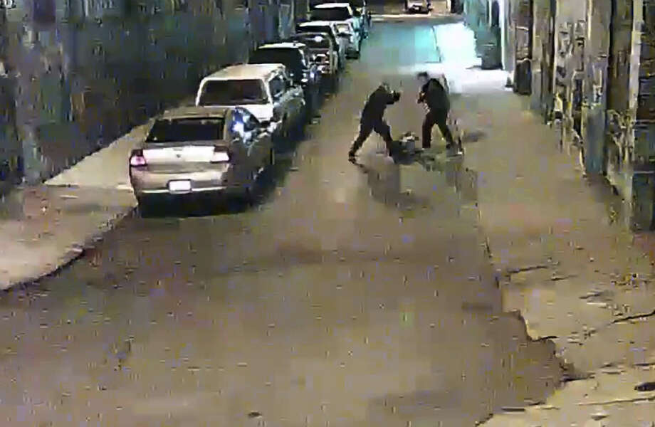 Two Alameda County Sheriff deputies are shown beating a man on a street in San Francisco's Mission District in a video screen grab. Photo: Coutesy Of San Francsco Public Defenders Office / Courtesy San Francisco Public Defenders Office