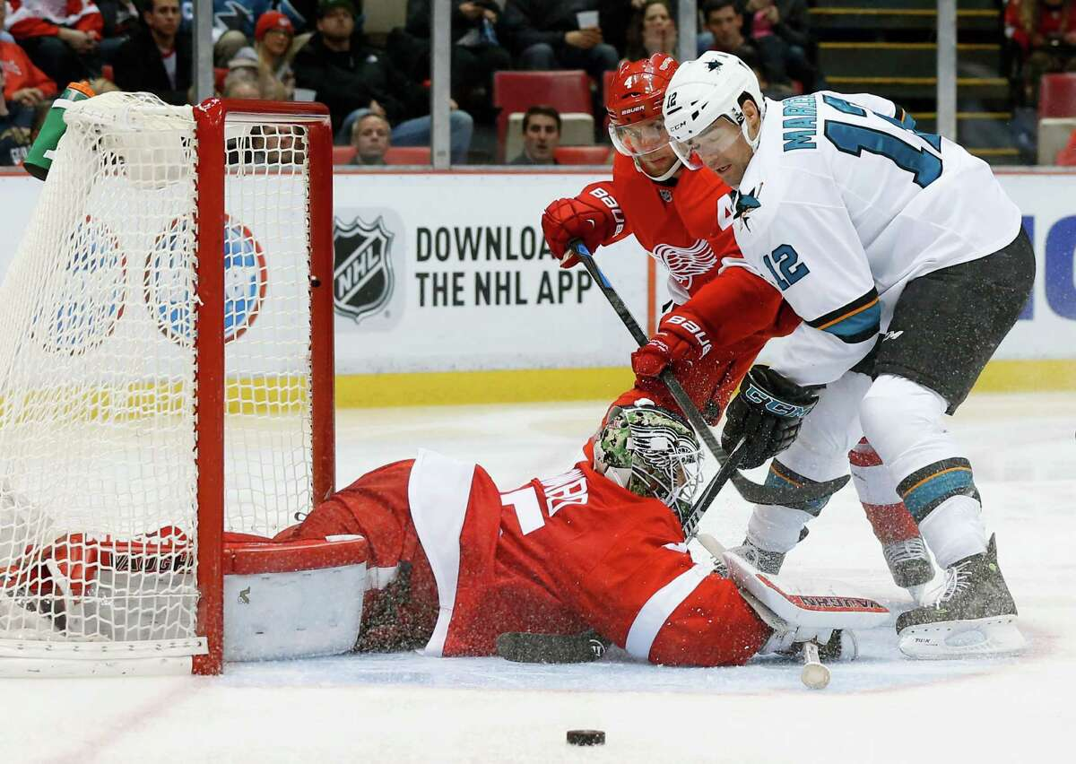 Detroit Red Wings goalie Jimmy Howard (35) stops a San Jose Sharks center Patrick Marleau (12) shot as Jakub Kindl (4) defends in the third period of an NHL hockey game Friday, Nov. 13, 2015 in Detroit. (AP Photo/Paul Sancya) ORG XMIT: MIPS111