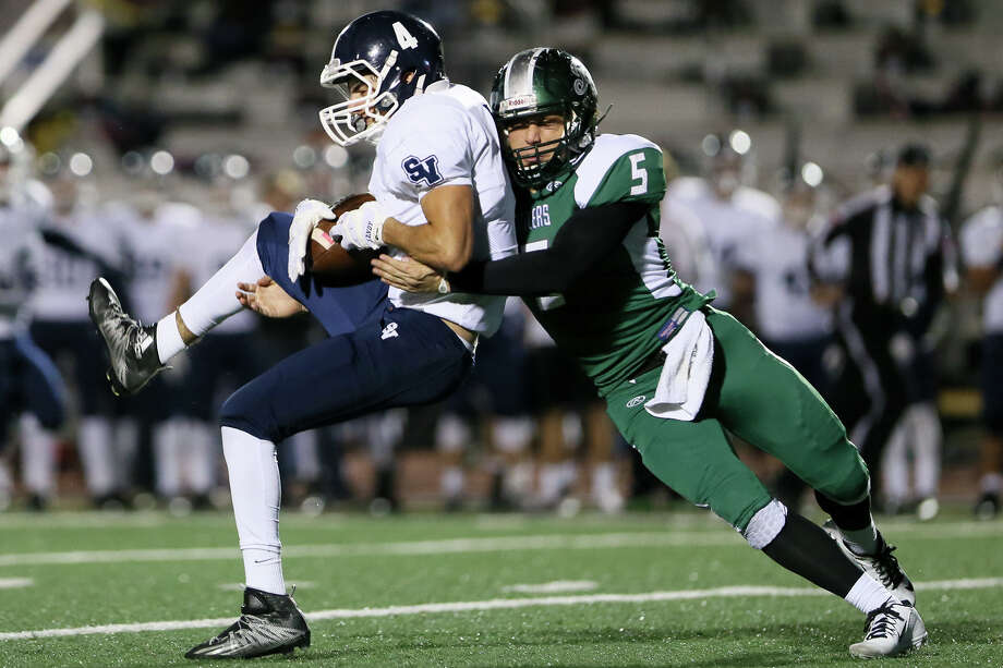 Smithson Valley's Matt Sandoval  is tackled by Reagan's Leyton Leone after making a first-down reception during the first half of their Class 6A Division I bidistrict game Friday at Comalander Stadium. Photo: Marvin Pfeiffer / San Antonio Express-News / Express-News 2015