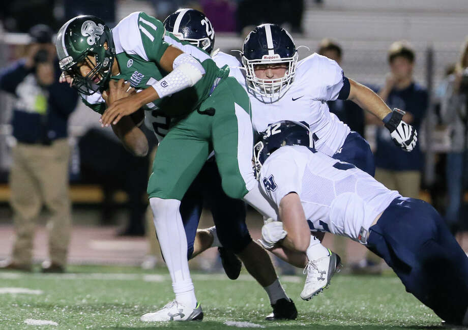 Reagan quarterback Kellen Mond (left) is brough down by Smithson Valley's AJ Singleton (from right), Jacob Staffier and Marquis Duncan during the first half of their Class 6A Division I bi-district game at Comalander Stadium on Friday, Nov. 13, 2015.  MARVIN PFEIFFER/ mpfeiffer@express-news.net Photo: Marvin Pfeiffer, Staff / San Antonio Express-News / Express-News 2015