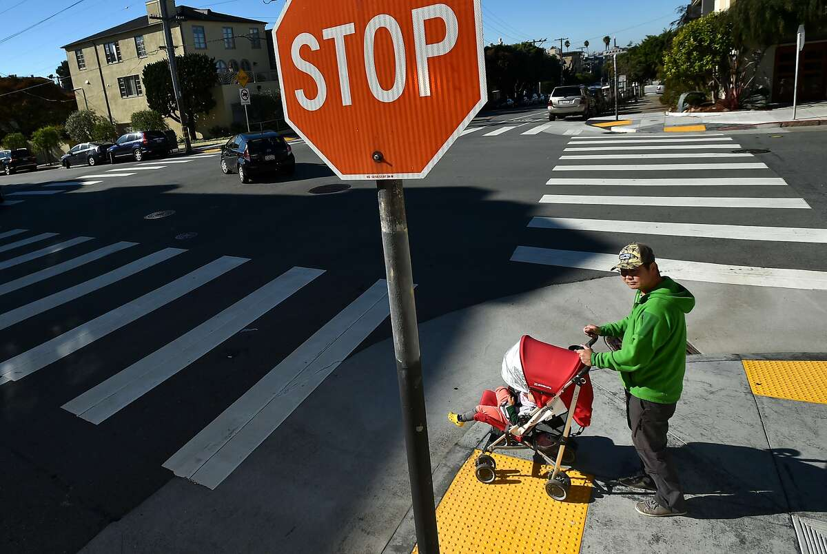 Soren Kim waits to cross the street at the intersection with his daughter Emma, 2, where his other daughter, 3-year-old Grace, was struck by a car in San Francisco on November 13, 2015. Since Grace has been hospitalized, three other people - including two 12-year-old boys - have been seriously injured on San Francisco streets.