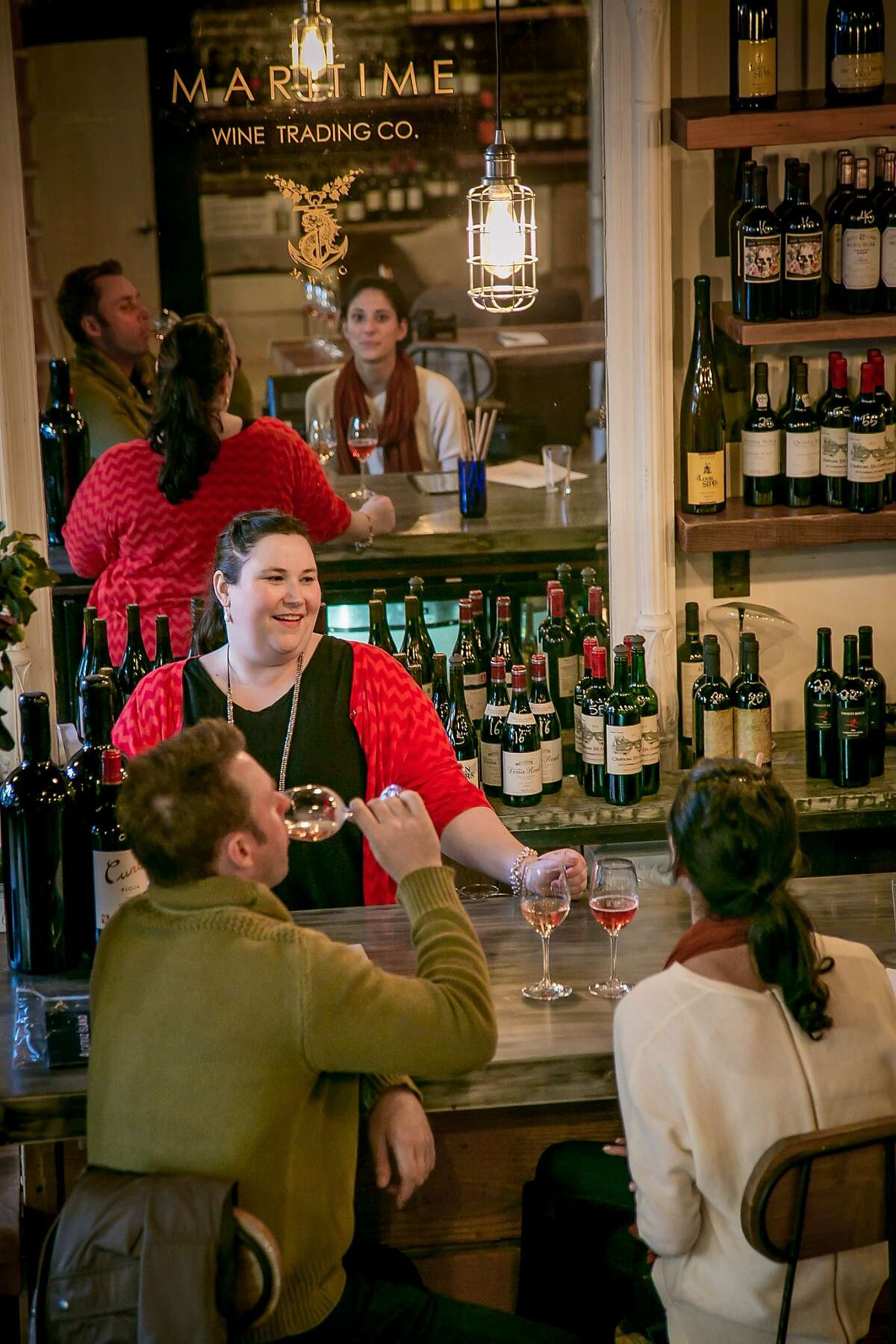 Manager Katie Guiney talks with a couple at the cozy Maritime Wine Tasting Studio on Columbus Avenue in S.F.