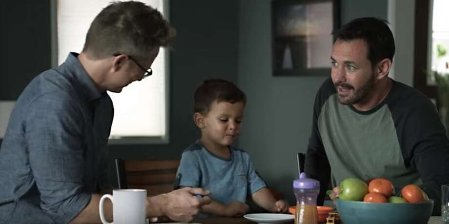 This screenshot from a Campbell's Soup commercial shows two dads feeding their son while making Darth Vader impressions.
