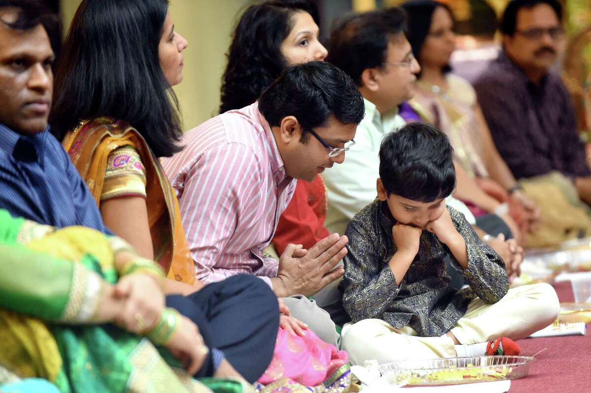 Soham Shah, 5, of East Greenbush, center, learns a ritual from his father, Sachin Shah, during the Grand Diwali Celebration on Saturday, Nov. 14, 2015, at the Hindu Temple Society in Loudonville, N.Y. (Cindy Schultz / Times Union)