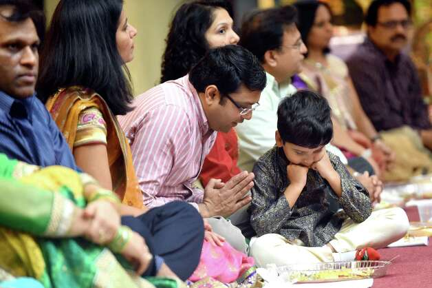 Soham Shah, 5, of East Greenbush, center, learns a ritual from his father, Sachin Shah, during the Grand Diwali Celebration on Saturday, Nov. 14, 2015, at the Hindu Temple Society in Loudonville, N.Y. (Cindy Schultz / Times Union) Photo: Cindy Schultz / 00034232A