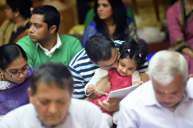 Deekshi Kandula, 8, of Franklin Mass., center, and her father, Venkat Kandula, share a loving moment during the Grand Diwali Celebration on Saturday, Nov. 14, 2015, at the Hindu Temple Society in Loudonville, N.Y. (Cindy Schultz / Times Union) Photo: Cindy Schultz / 00034232A