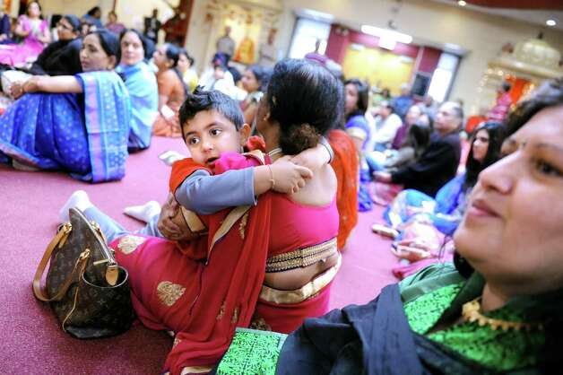 Aryan Patel, 3, center, embraces his grandmother Kiran Amin of Scotia as they listen to music during the Grand Diwali Celebration on Saturday, Nov. 14, 2015, at the Hindu Temple Society in Loudonville, N.Y. (Cindy Schultz / Times Union) Photo: Cindy Schultz / 00034232A