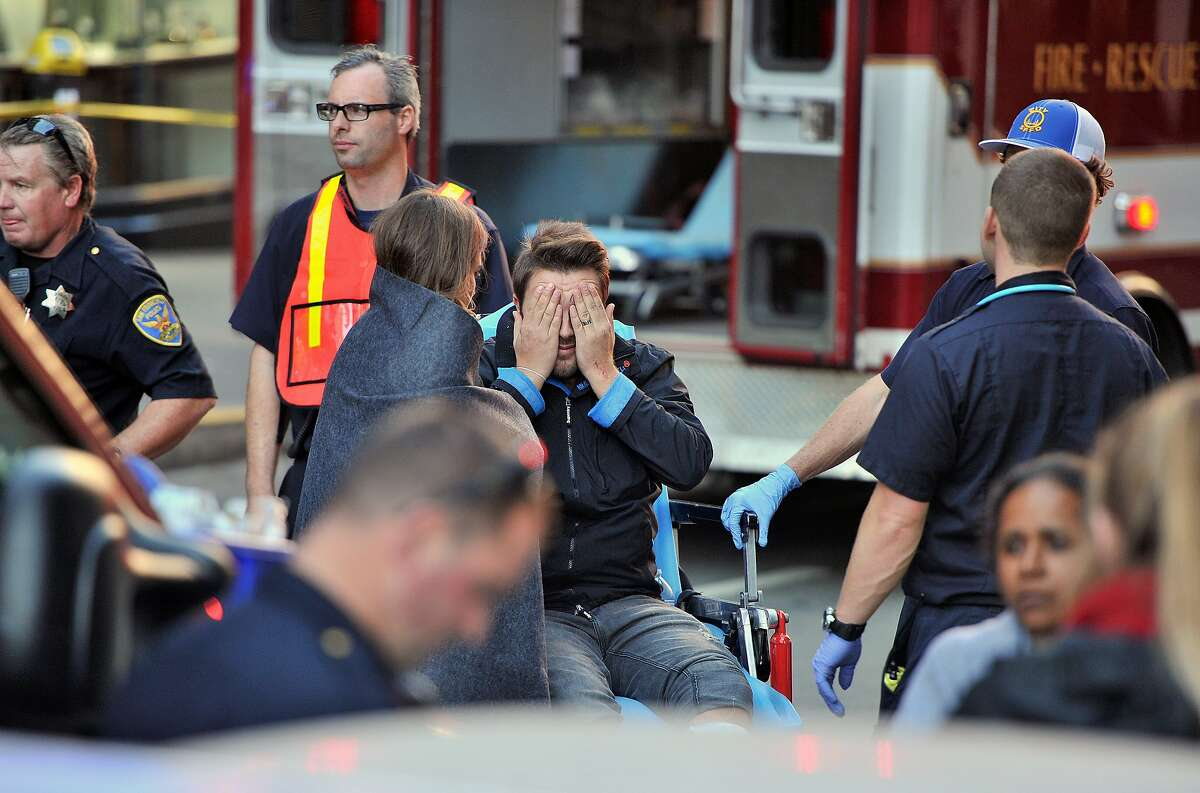 An injured man reacts after being involved in a crash near Union Square in San Francisco, Calif. on Friday, Nov. 13, 2015. According to The San Francisco Fire Department, a double-decker tour bus crashed into multiple vehicles and pedestrians. (AP Photo/Josh Edelson)
