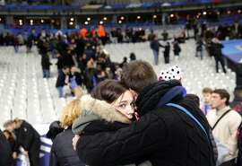 Spectators embrace each other as they stand on the playing field of the Stade de France stadium at the end of a friendly soccer match between France and Germany in Saint Denis, outside Paris, Friday, Nov. 13, 2015. Hundreds made their way to the pitch after explosions were heard nearby. Multiple fatal attacks throughout the city have prompted President Francois Hollande to announce he was closing the country's borders and declaring a state of emergency. (AP Photo/Christophe Ena)