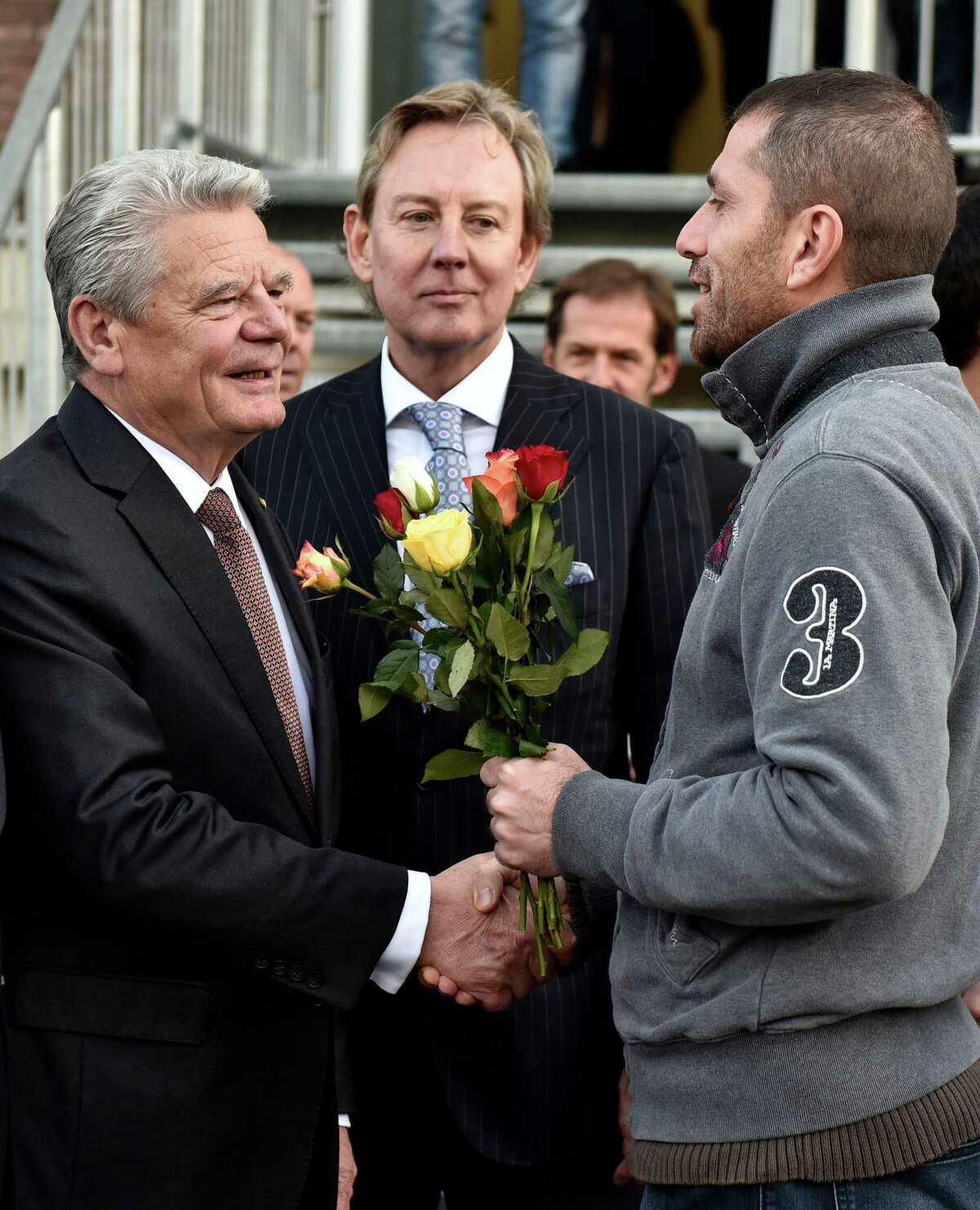 German president Joachim Gauck, left, receives flowers from a migrant during his visit of a migrant shelter in Bergisch Gladbach, western Germany, Thursday, Nov. 12, 2015. (AP Photo/Martin Meissner) ORG XMIT: MME101