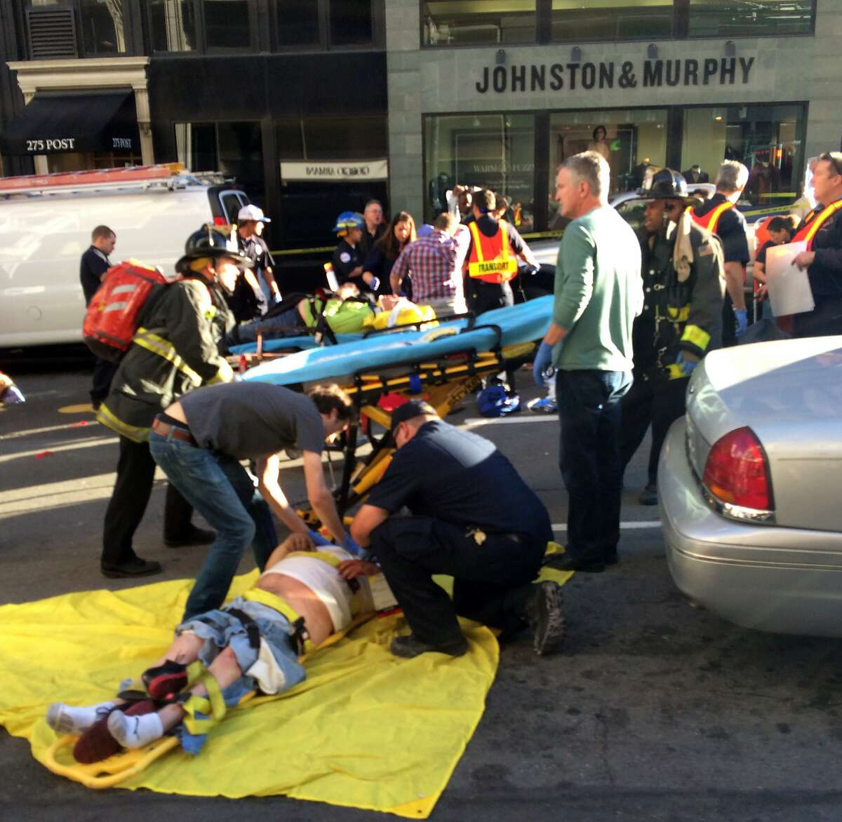 Emergency personnel tend to the injured after a double-decker tour bus smashed into a bicyclist, several cars and a construction site Friday, Nov. 13, 2015, in San Francisco's tourist-packed Union Square. Authorities say at least 19 were injured, including five critically. (Hoda Emam via AP)