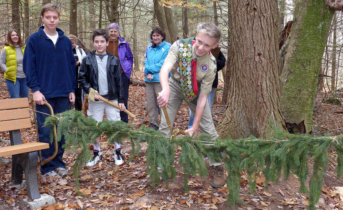 Michael Beskid and his fellow boy scouts from troop 525 cut a garland for a bridge they built for Michael's Eagle Scout Project. The bridge spans the Black Brook at Rensselaer Land Trust's Robert P. Ingalls Nature Preserve in Stephentown. (Allan Stern)