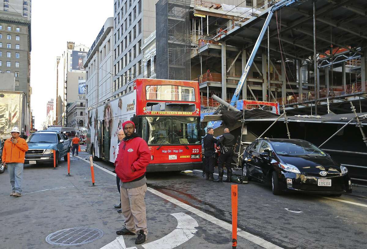 Bystanders look on next to an open-air tour bus, at right under scaffolding, that crashed into a construction site near Union Square Friday, Nov. 13, 2015, in San Francisco. Officials say there may have been as many as 30 people aboard the bus. There's no word on the conditions of the injured. (Mike Koozmin/San Francisco Examiner via AP)