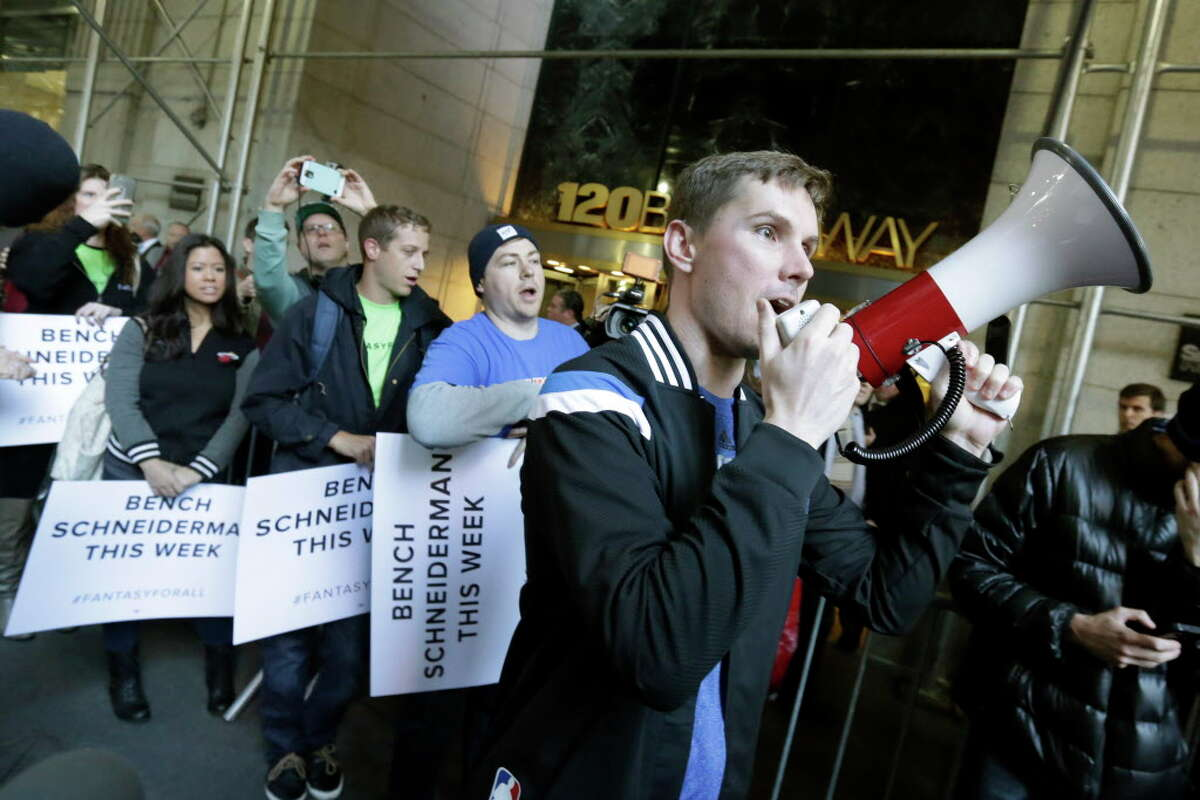 Geoff Bough, right, leads fantasy sports fans as they demonstrate outside the Financial District offices of New York state Attorney General Eric Schneiderman, in New York, Friday, Nov. 13, 2015. Schneiderman's decision that daily fantasy sports betting sites FanDuel and DraftKings are illegal gambling operations in his state is a blow to the companies, but the multibillion-dollar industry could have more legal headaches yet to come. (AP Photo/Richard Drew) ORG XMIT: NYRD120