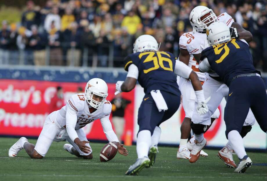 Texas quarterback Jerrod Heard (13) recovers a missed snap during the first half of an NCAA college football game against West Virginia, Saturday, Nov. 14, 2015, in Morgantown, W.Va. (AP Photo/Raymond Thompson) Photo: Ray Thompson, FRE / Associated Press / FR171247 AP