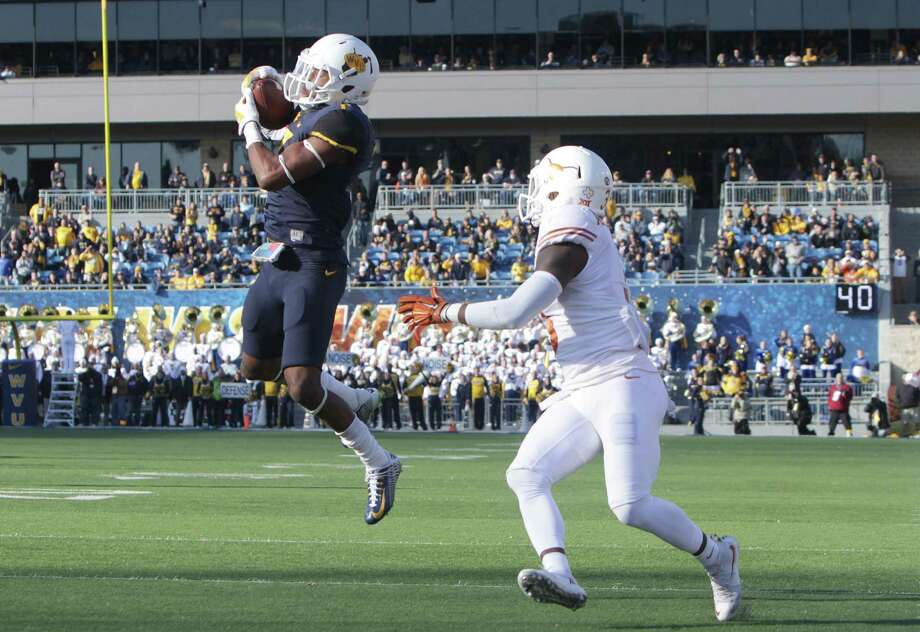 West Virginia cornerback Daryl Worley, left, intercepts a pass intended for Texas wide receiver Armanti Foreman (3) during the second half of an NCAA college football game, Saturday, Nov. 14, 2015, in Morgantown, W.Va. (AP Photo/Raymond Thompson) Photo: Ray Thompson, FRE / Associated Press / FR171247 AP
