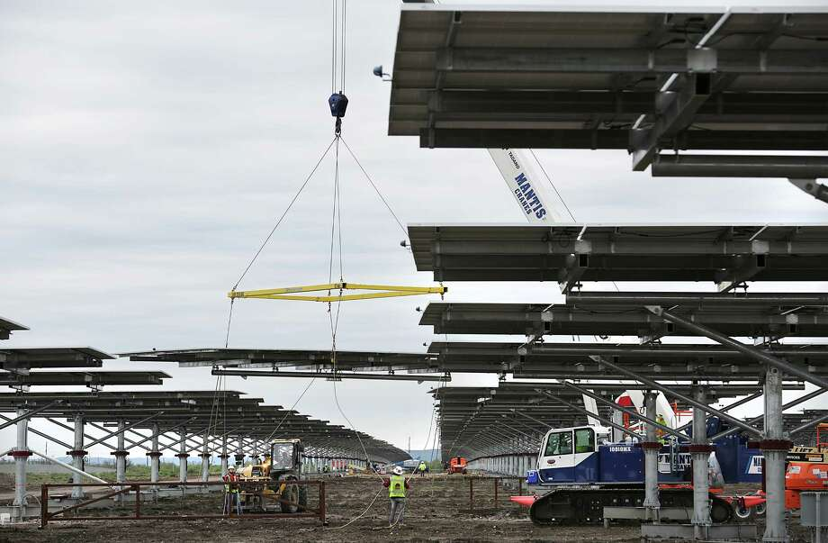 Workers lift a table of panels to be placed on a pedestal foundation at CPS Energy's Alamo 5 Solar Farm near Uvalde. Photo: Bob Owen /San Antonio Express-News / San Antonio Express-News