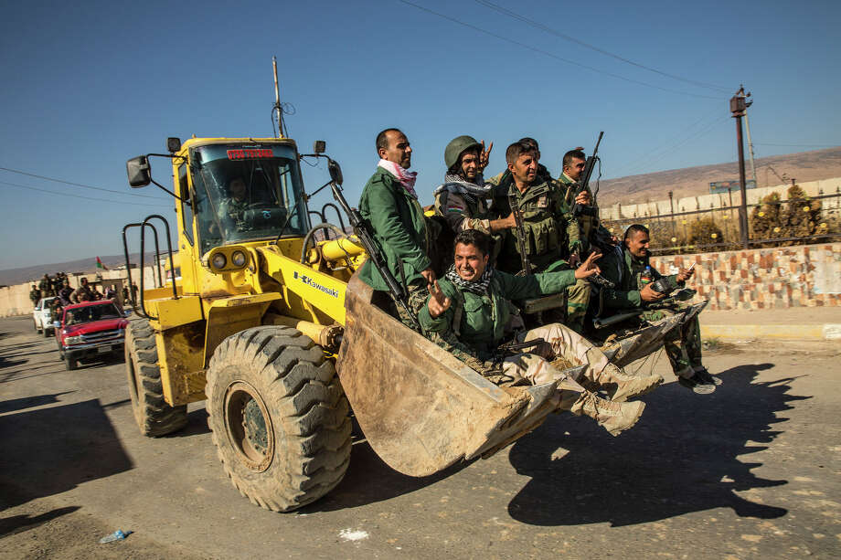 Kurdish fighters, known as peshmerga, ride in a bulldozer while celebrating the retaking Sinjar, Iraq, on Friday. Yazidi fighters helped the Kurds regain control of the city from the Islamic State. Photo: BRYAN DENTON / / NYTNS
