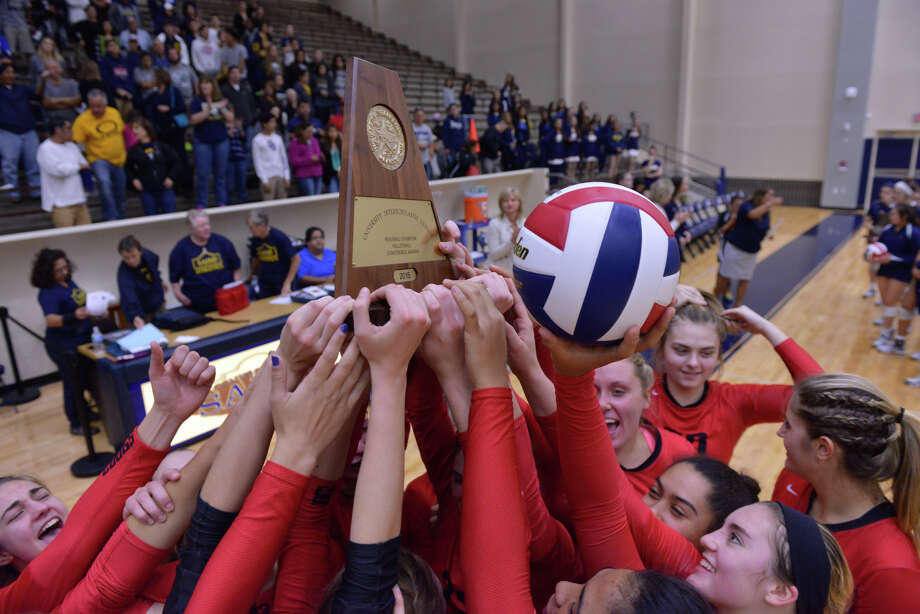 New Braunfels Canyon players hoist the trophy after defeating O'Connor to win the U.I.L Region IV  6A volleyball tournament Saturday afternoon. Photo: Robin Jerstad / San Antonio Express-News