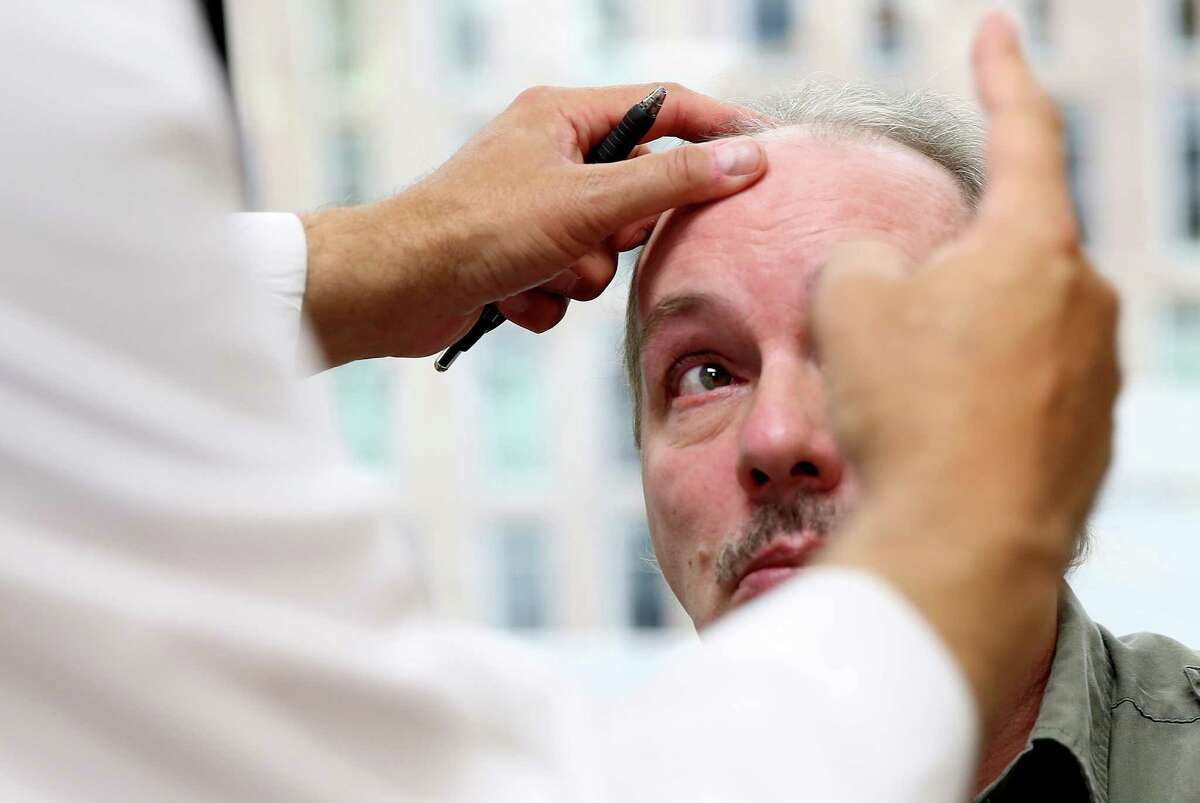 Dr. David Baskin checks the movement in former brain cancer patient Matt Futer's eyes during an appointment. Futer was successfully treated with viral immunotherapy at Houston Methodist Hospital almost a decade ago. Baskin's original prognosis gave Futer a 20 percent of living longer than a year.
