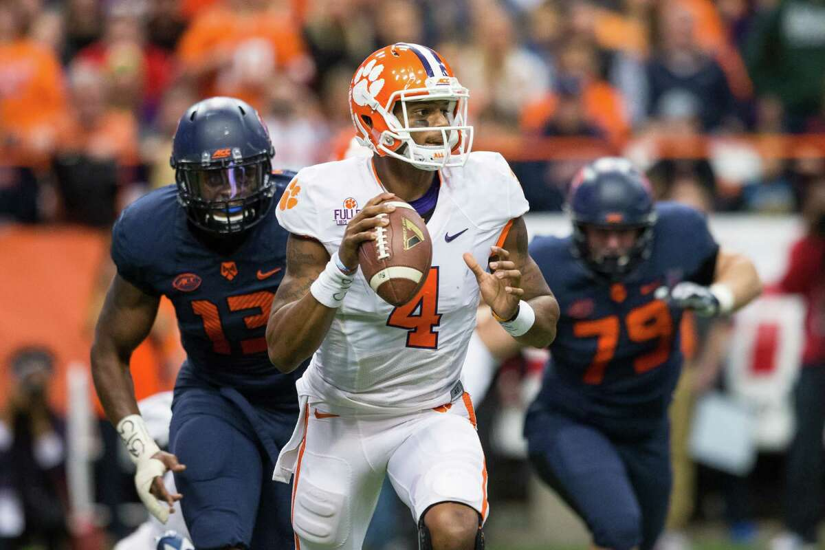 SYRACUSE, NY - NOVEMBER 14: Deshaun Watson #4 of the Clemson Tigers scrambles as Syracuse Orange defenders pursue on November 14, 2015 at The Carrier Dome in Syracuse, New York. Clemson defeats Syracuse 37-27. (Photo by Brett Carlsen/Getty Images) ORG XMIT: 585634801