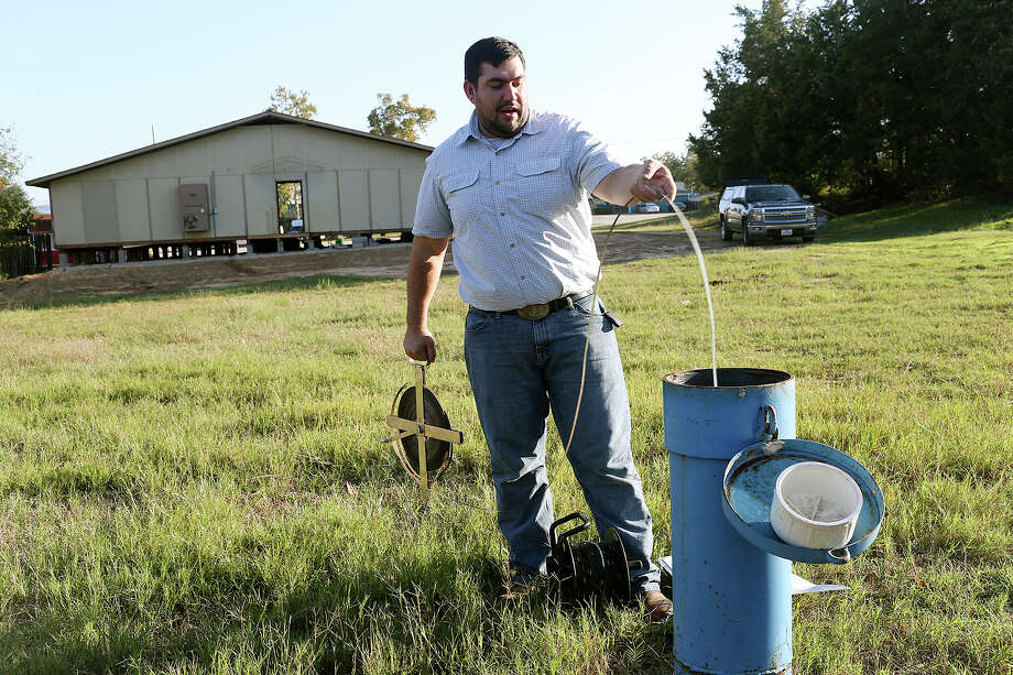 Bobby Bazan, water resource management specialist with Post Oak Savannah Groundwater Conservation District, measures Monitoring Well 9166 in Milano on Nov. 3. The district regulates the pumping of groundwater in part of the Carrizo-Wilcox Aquifer. That is the aquifer San Antonio wants to tap as a new water source and would pipe the water 142 miles from Burleson County. Photo: Jerry Lara /San Antonio Express-News / © 2015 San Antonio Express-News