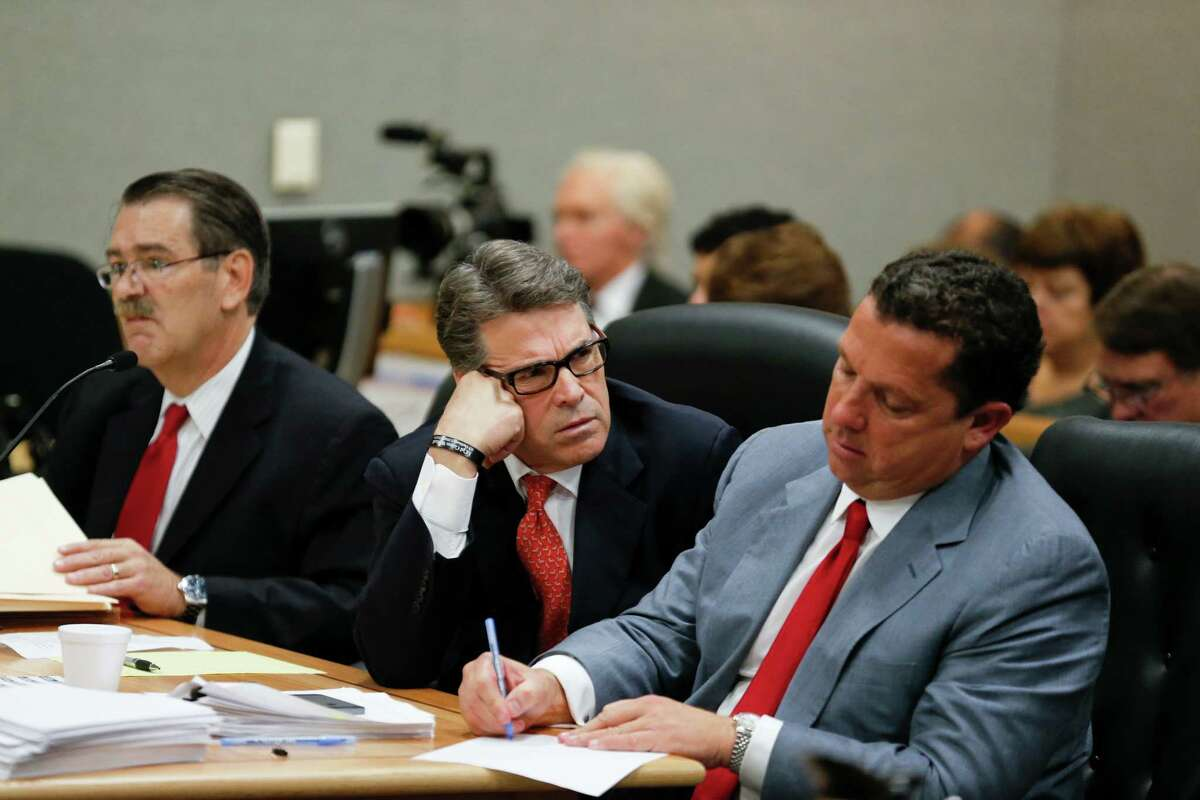 Rick Perry peers at defense lawyer Tony Buzbee during an appearance in Travis County Court to answer charges in an indictment regarding his veto.