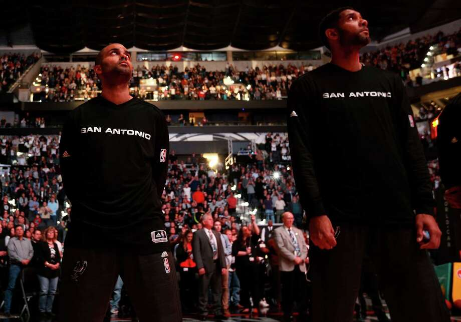 Spurs guard Tony Parker (left) joined by teammate Tim Duncan look up during the playing of the France National Anthem in respect to the country after recent terrorist attacks. Parker and fellow teammate Boris Diaw are both French citizens. Photo: Kin Man Hui, San Antonio Express-News / ©2015 San Antonio Express-News