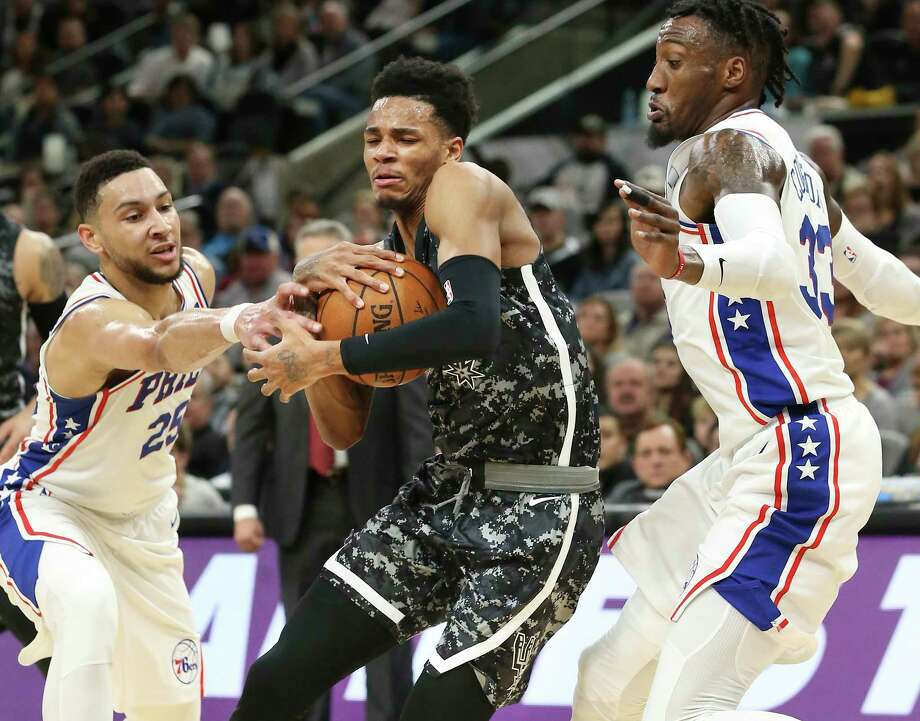 Dejounte Murray tries to squeeze between Ben Simmons (25) and Robert Covington as the Spurs host Philadelphia at the AT&T Center  on January 26, 2018. Photo: Tom Reel, San Antonio Express-News / 2017 SAN ANTONIO EXPRESS-NEWS