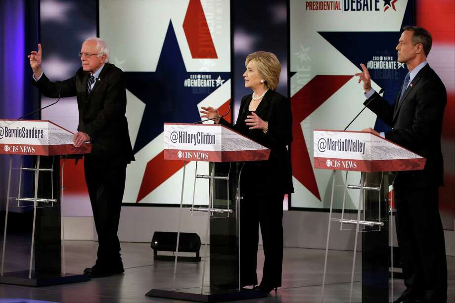 Democratic candidates Bernie Sanders, left, Hillary Rodham Clinton and Martin O'Malley showed a foreign policy split Saturday, a day after deadly terrorist attacks in Paris. Sanders argued for a hands-off approach, while Clinton called for a more aggressive U.S. role in Syria. Photo: Charlie Neibergall, STF / AP