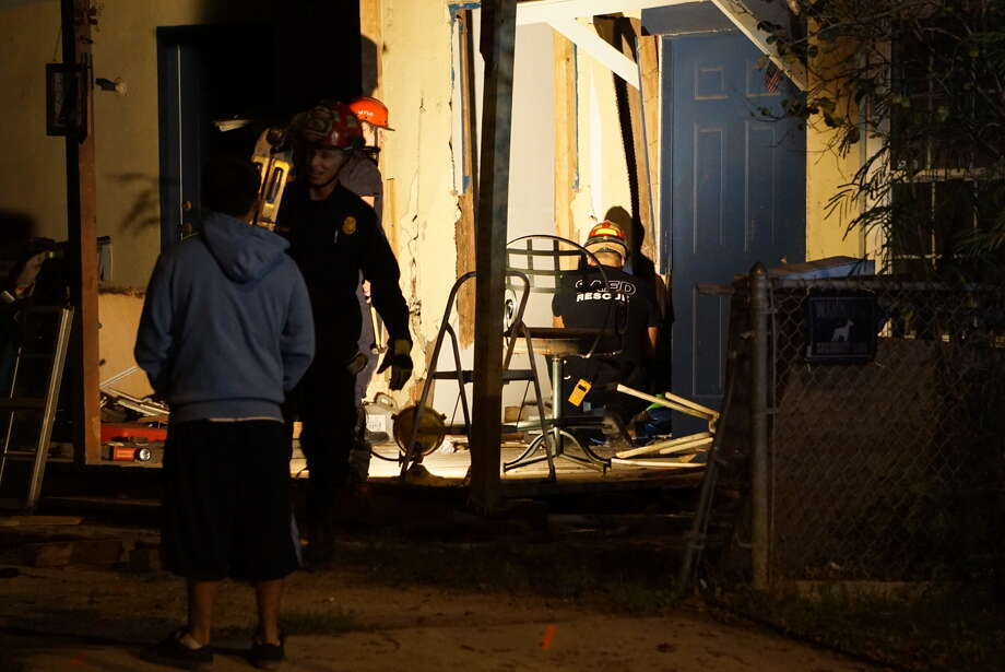 San Antonio Police investigate the scene of a crash on the West Side where they say a driver slammed into a home after hitting a pedestrian. Photo: By Jacob Beltran, San Antonio Express-News