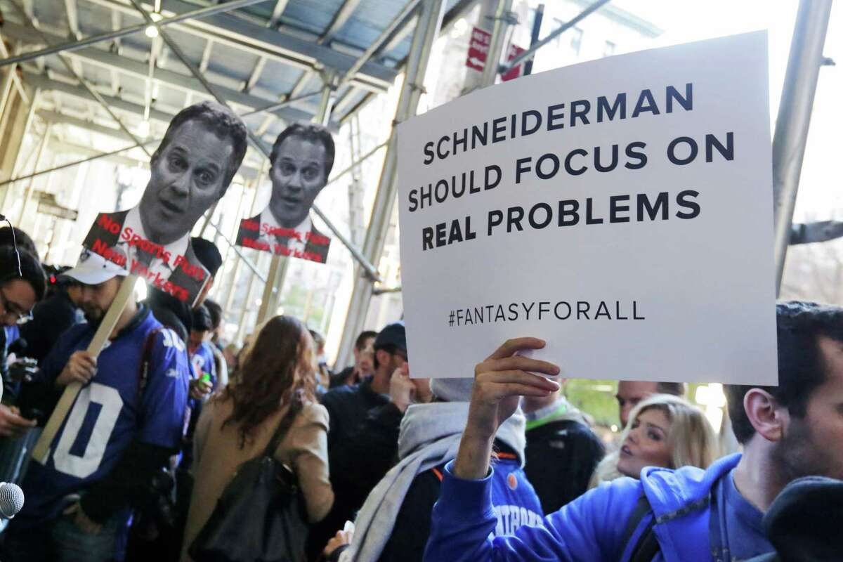 Fantasy sports fans demonstrate outside the Financial District offices of New York state Attorney General Eric Schneiderman, in New York, Friday, Nov. 13, 2015. Schneiderman's decision that daily fantasy sports betting sites FanDuel and DraftKings are illegal gambling operations in his state is a blow to the companies, but the multibillion-dollar industry could have more legal headaches yet to come. (AP Photo/Richard Drew) ORG XMIT: NYRD105